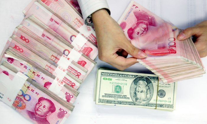A clerk counts stacks of Chinese yuan and U.S. dollars at a bank in Shanghai, China. (China Photos/Getty Images)