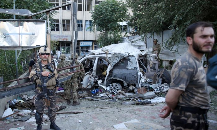 In this Saturday, Aug. 22, 2015 file photo, Afghan security forces and British soldiers inspect the site of a suicide attack in the heart of Kabul, Afghanistan. (AP Photo/Massoud Hossaini)