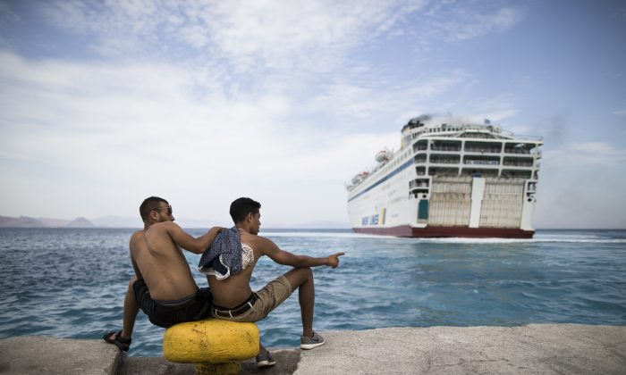 Two migrants look toward a giant passenger ferry while it arrives at the Greek holiday island of Kos, to provide temporary accommodation for some thousands of refugees sleeping rough after crossing clandestinely from Turkey in flimsy boats, Greece, Friday, Aug. 14, 2015. (AP Photo/Alexander Zemlianichenko)