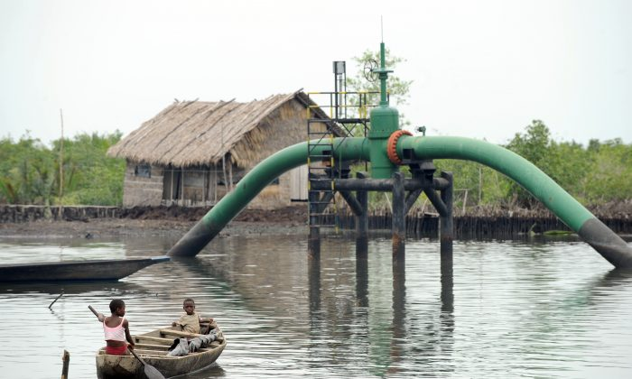 Children sail past an oil pipeline head near their home at Andoni, a settlement in the Rivers State, Nigeria, on April 12, 2011. (Pius Utomi Ekpei/AFP/Getty Images)