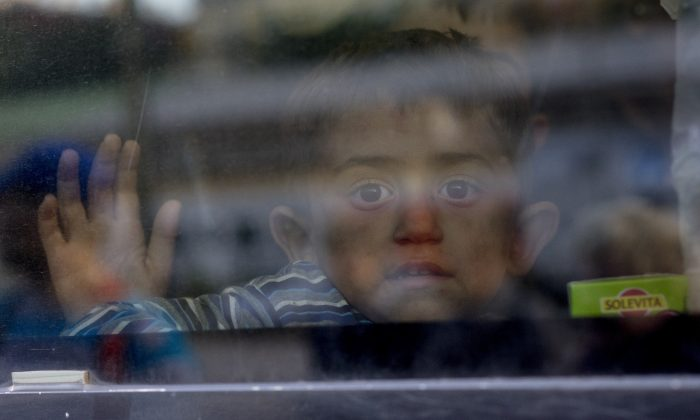 A refugee children waves goodbye, from a train going to Munich, to volunteers who helped them at Vienna's Westbahnhof train station in Vienna, Austria, Sept. 6, 2015. Thousands of migrants and refugees have transited from Hungary via Vienna where they were welcomed and helped by volunteers in the last couple of days. (Joe Klamar/AFP/Getty Images)