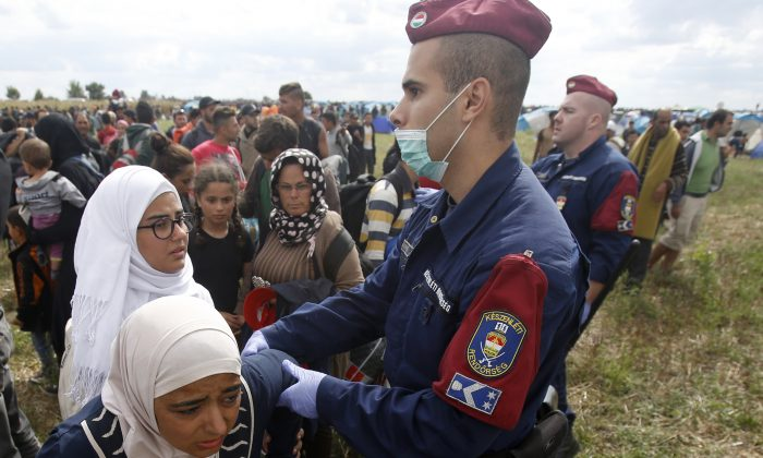 Hungarian police officers stop a group of migrants near a temporary holding center for asylum seekers in Roszke, southern Hungary, Tuesday, Sept. 8, 2015. Hungarian police stood by as thousands of migrants hopped cross-border trains Sunday into Austria, taking advantage of Hungary's surprise decision to stop screening international train travelers for travel visas, a get-tough measure that the country had launched only days before to block their path to asylum in Western Europe. (AP Photo/Darko Vojinovic)