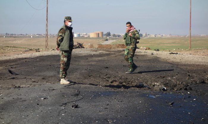 Kurdish soldiers survey the site of a bomb attack on a road between Mosul, Iraq, and the Syrian border in northern Iraq. Kurdish authorities in Iraq said they have evidence the Islamic State used chlorine gas as a chemical weapon against Peshmerga fighters. (Kurdistan Region Security Council/AP)