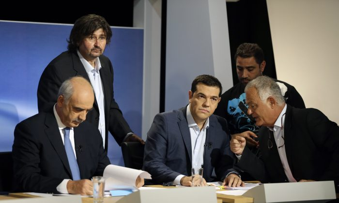 The leader of the left-wing Syriza party and former Greek Prime Minister Alexis Tsipras, second, right, listens to ERT CEO Lambis Tagmatarhis, right, as main opposition conservative New Democracy head Vangelis Meimarakis, left, reads his notes before a live televised debate at the state-run ERT television in Athens, Wednesday, Sept. 9, 2015. The leaders of all but one of Greece's main political parties hold a live televised debate for the first time in six years on Wednesday night before the country's Sept. 20 early election. (AP Photo/Thanassis Stavrakis)