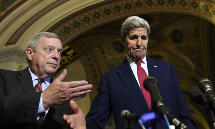 Secretary of State John Kerry, left, listens as Sen. Richard Durbin, D-Ill., right, speaks to reporters following their meeting on Capitol Hill in Washington, Wednesday, Sept. 9, 2015, on the Iran nuclear deal. (AP Photo/Susan Walsh)