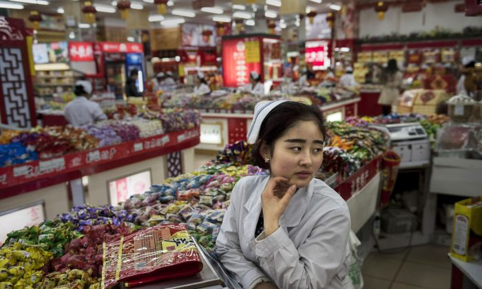 A Chinese worker waits for customers at a grocery store on January 20, 2015 in central Beijing, China. (Kevin Frayer/Getty Images)