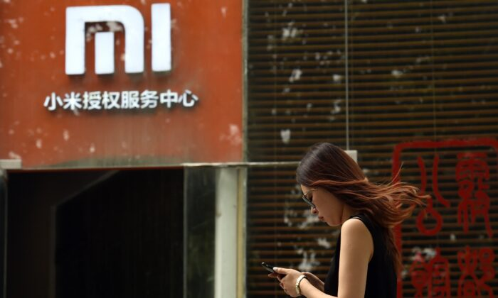A woman walks past a Xiaomi logo outside a Xiaomi service center in Beijing, China, on Aug. 5, 2015. (Greg Baker/AFP/Getty Images)