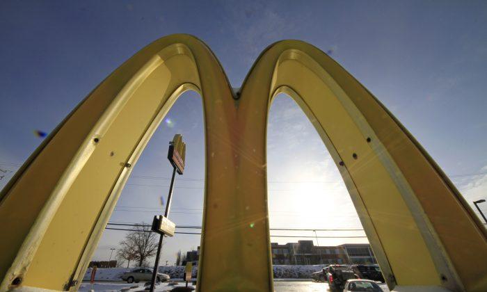Cars drive past the McDonald's Golden Arches logo at a McDonald's restaurant in Robinson Township, Pa., on Jan. 21, 2014. (AP Photo/Gene J. Puskar)