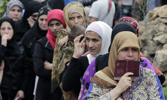 Syrian women wait in line to receive aid from an Islamic relief agency at a refugee camp in the town of Ketermaya, north of the port city of Sidon, Lebanon on Sept. 7, 2015 file photo. (AP Photo/Bilal Hussein)