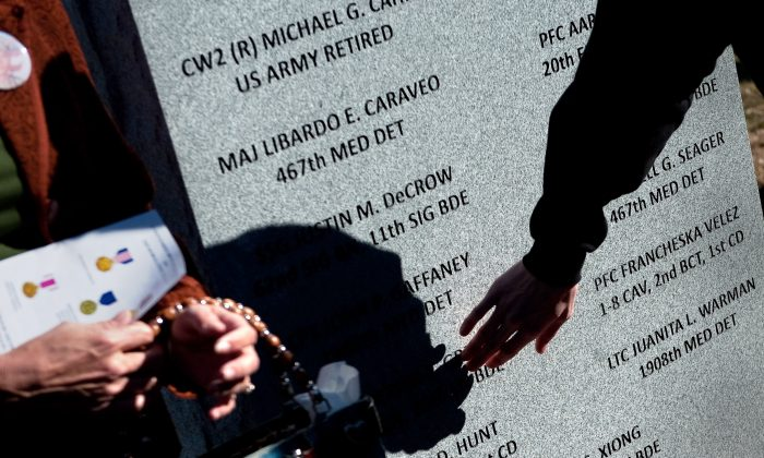 Family members and friends visit a memorial stone after it was unveiled during a Nov. 5, 2010, ceremony commemorating the one-year anniversary of the shootings on Fort Hood, Texas. (D. Myles Cullen/U.S. Department of Defense)