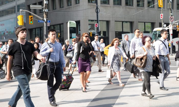 People head to work in Toronto on the morning of July 14, 2015. A new survey suggests many Canadians are pessimistic about their financial futures and expect to work longer than originally planned before retiring. (Photo by Don Quincy)