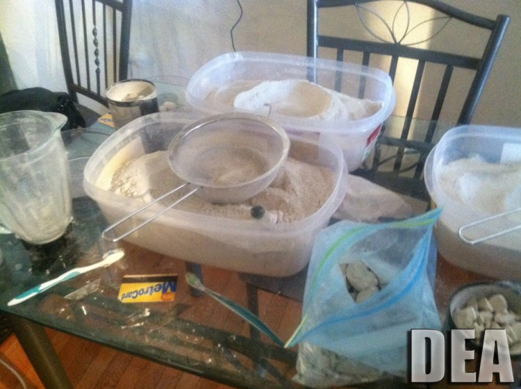 Heroin seen in containers with a foundation of a grinder, a sifter, and other drug selling tools. (DEA)