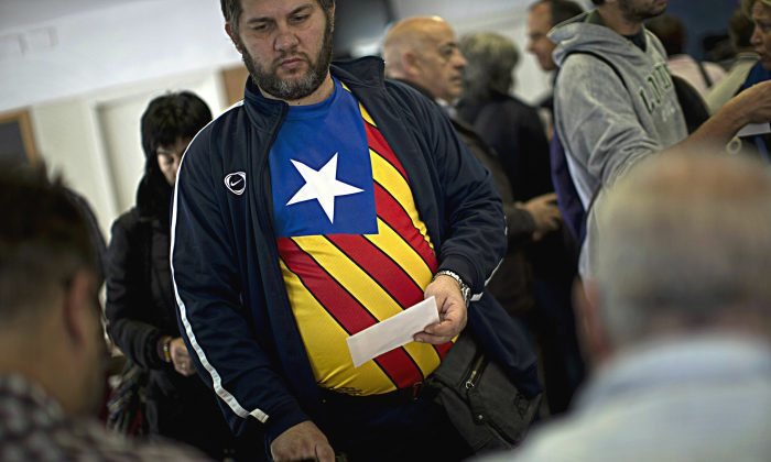 Carlas Albert, 45, waits to cast his vote for an informal independence poll in a polling station in Barcelona, Spain, on Sunday Nov.9, 2014. (AP Photo/Emilio Morenatti)
