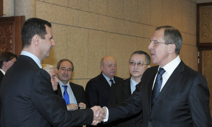FILE - In this Feb. 7, 2012 file photo, Syrian President Bashar Assad, left, shakes hands with Russian Foreign Minister Sergey Lavrov after talks in Damascus, Syria. Lavrov said Thursday, Sept. 10, 2015, that Russian aircraft flying into Syria have been delivering weapons along with humanitarian supplies. (AP Photo/Pool, File)