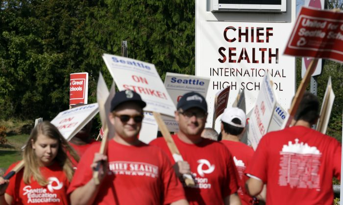 Teachers walk a picket line in front of Chief Sealth International High School Wednesday, Sept. 9, 2015, in Seattle. (AP Photo/Elaine Thompson)