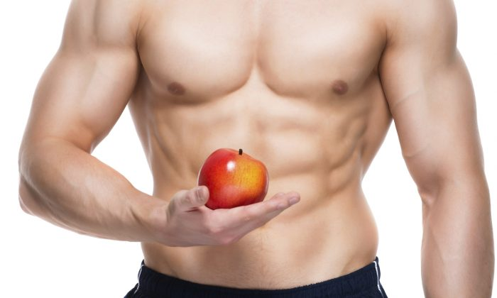 Young man with perfect body holding red apple in his hand - isolated on