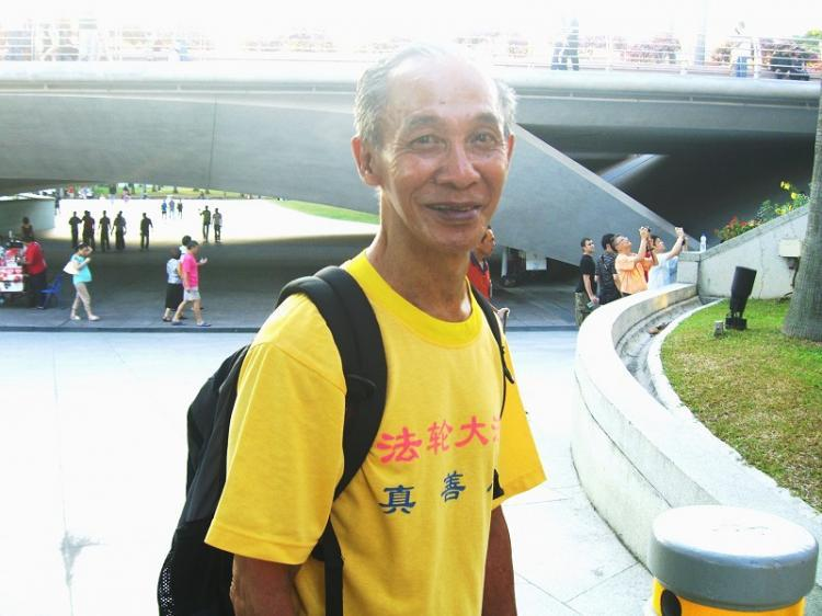 Mr. Chua Eng Chwee, 71, has gone to a tourist site everyday for the past 10 years to pass materials about the persecution of Falun Gong. (Huang Siyuan/The Epoch Times)
