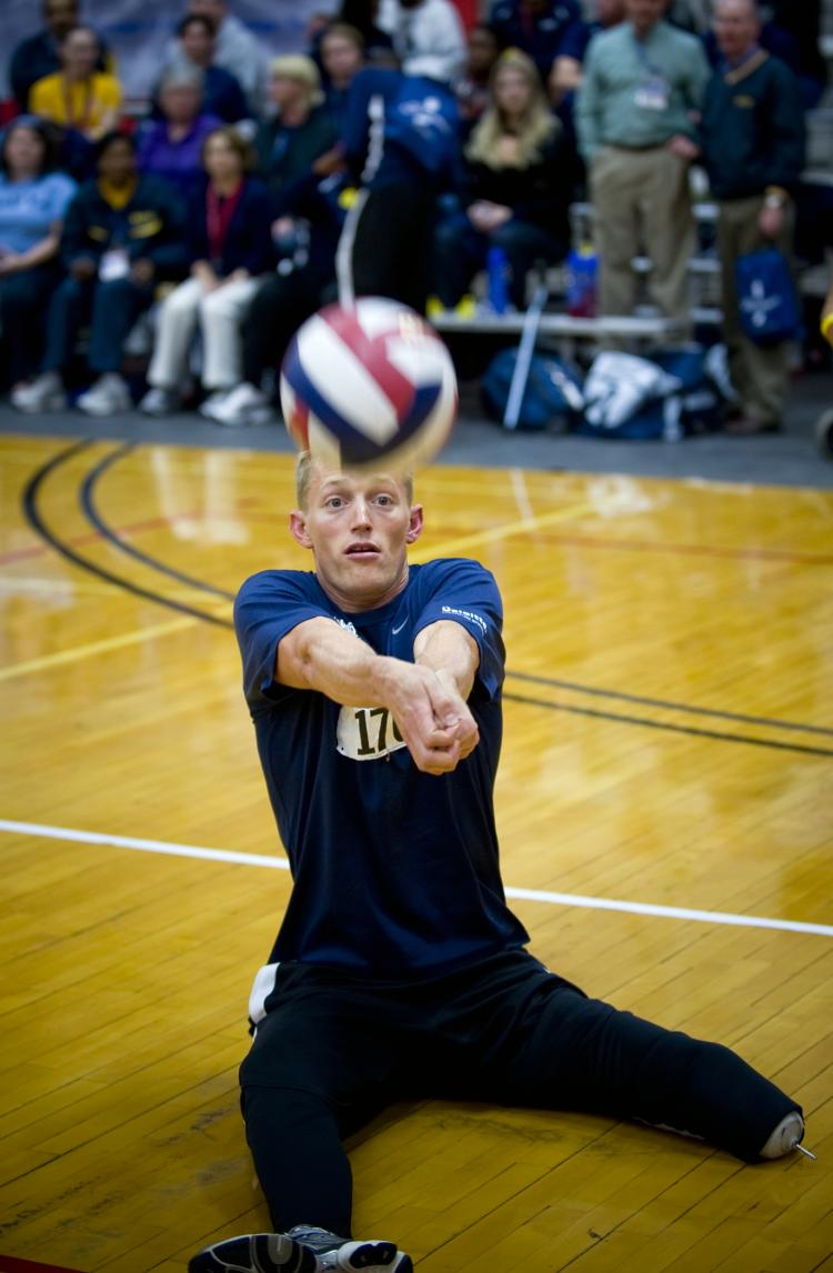 U.S. Navy Parachute Rigger 3rd Class Michael Johnston bump passes the ball to a teammate during a sitting volleyball game against Army.  (Photo by MC1 R. Jason Brunson)
