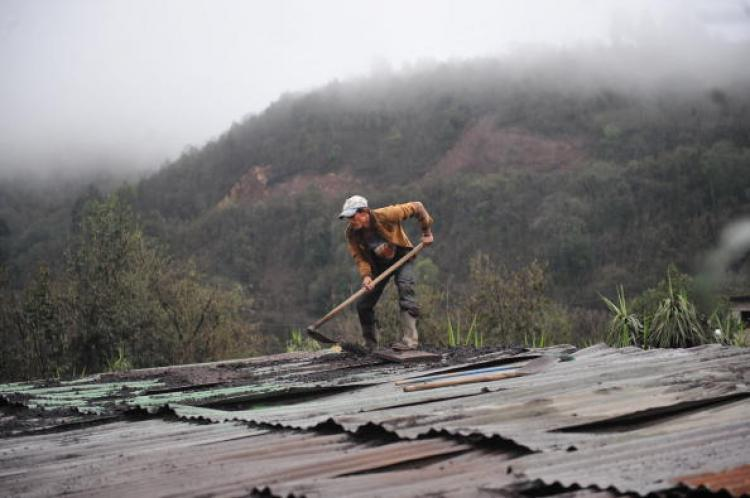 A man cleans the roof of his home of ashes from the Pacaya volcano, some 50 km (31 miles) south of Guatemala City, in Las Calderas, San Vicente Pacaya, Guatemala.  (Johan Ordonez/Getty Images)