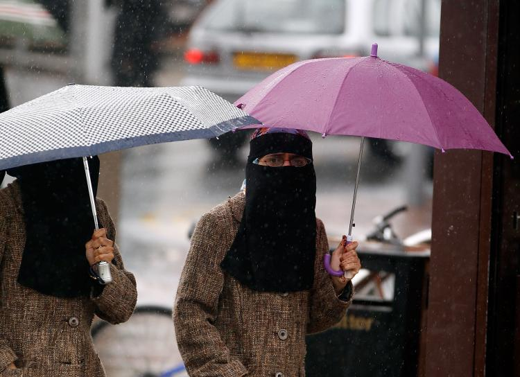 Women, sheltering under umbrellas, wear full face Niqab on the streets of Blackburn July 20, 2010 in Blackburn, England. (Christopher Furlong/Getty Images)
