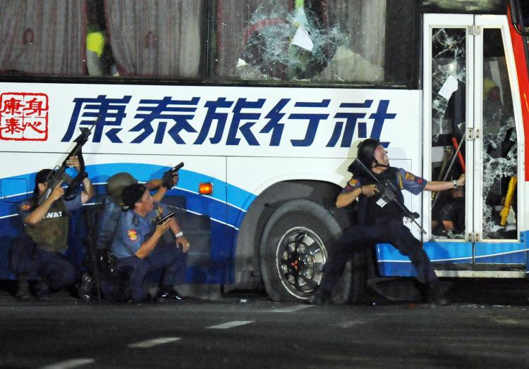Philippine policemen take position as they start their attack on the tourist bus hijacked in Manila on August 23, 2010. (Ted Aljibe/AFP/Getty Images)