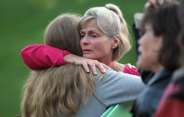 Residents evacuated due to wildfire embrace before a community meeting September 8, in Boulder, Colorado. More than 140 structures, many of them houses, were destroyed, along with 6,000 acres burnt in the Fourmile Canyon fire to the west of Boulder. (John Moore/Getty Images)
