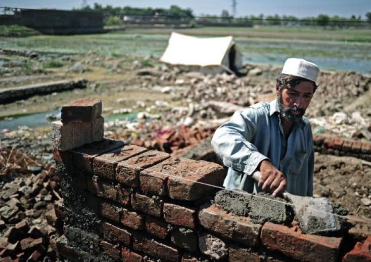 A Pakistani man begins to rebuild his home in Nowshera on September 21. United Nation aid agencies have warned that flood stricken areas of Pakistan face a looming threat of child malnutrition.  (Carl de Souza/Getty Images )