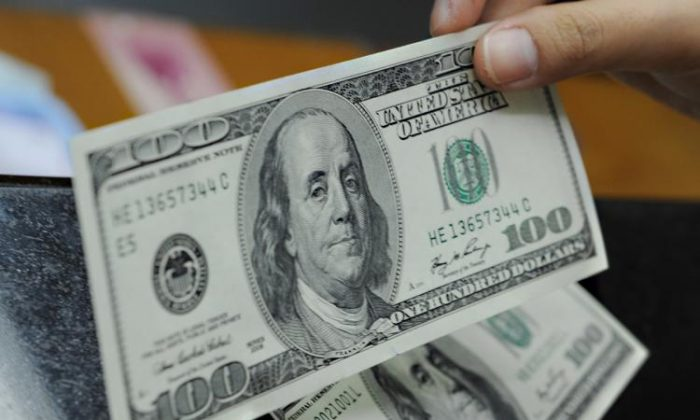 A customer holds $100 notes in a file photo. (Adek Berry/AFP/Getty Images)