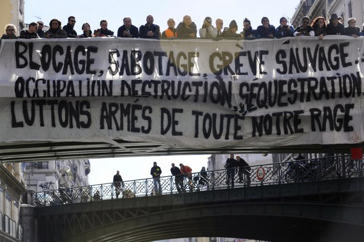 People stand behind a giant banner hanging on a bridge on Oct. 19 in Marseille, during a demonstration against the governmental pension reform. (Anne-Christine Poujoulat/AFP/Getty Images)