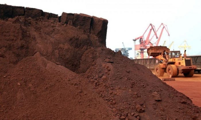 A man, driving a front loader, shifts soil containing rare earth minerals to be loaded for export to Japan at a port in Lianyungang, east China's Jiangsu Province, September 2010. (STR/AFP/Getty Images)