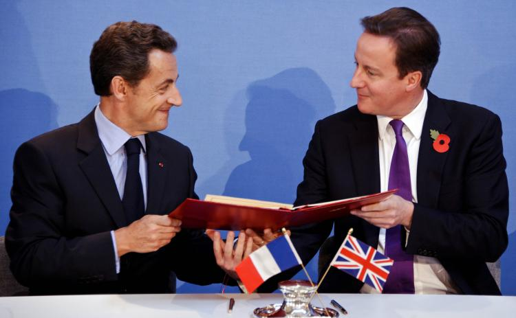French President Nicolas Sarkozy (L) and Prime Minister David Cameron exchange copies after signing a treaty during the Anglo-French summit at Lancaster House on Nov. 2 in London, England. (Lionel Bonaventure/Getty Images)