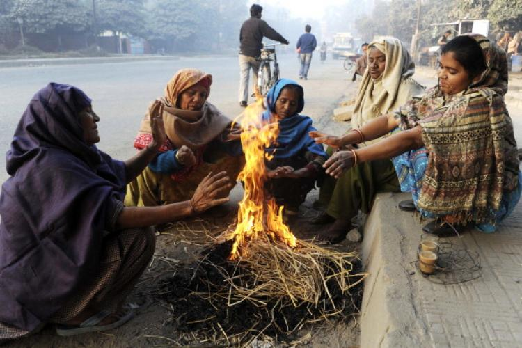 Indian street sweepers warm themselves as they sit around a bonfire on a roadside in Amritsar on Dec. 3, 2010. (Narinder Nanu/AFP/Getty Images)
