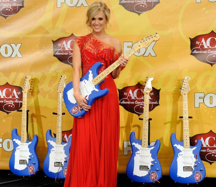 Carrie Underwood poses in the press room with guitar trophies she won at the American Country Awards at the MGM Grand Garden Arena December 6, in Las Vegas, Nevada. (Ethan Miller/Getty Images)