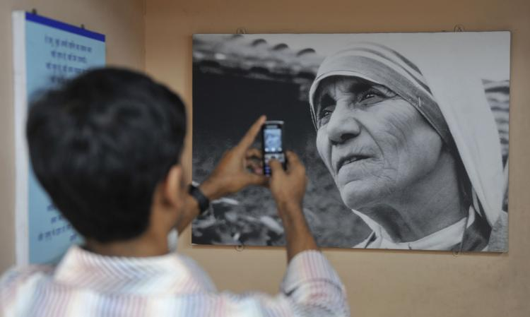 A boy takes a picture of an image of Mother Teresa that hangs in a carriage of the 'Mother Express' train in Mumbai. Research has found that witnessing extraordinary acts of compassion inspire others to do good in their own lives. (Sajjad Hussain/AFP/Getty Images)