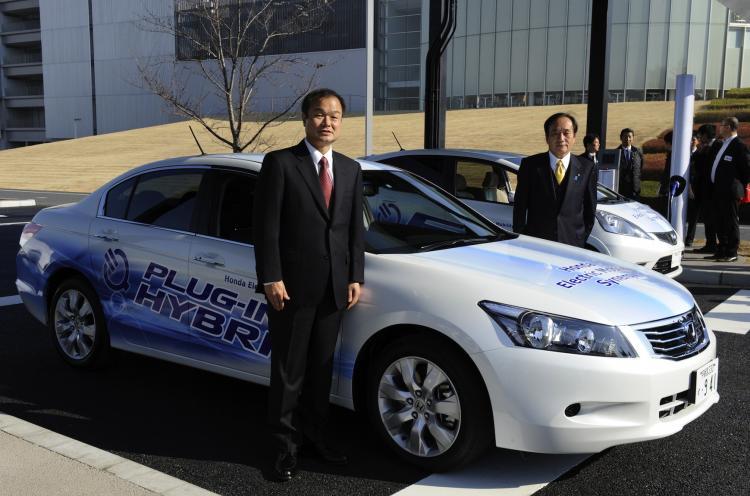 Honda Motors President Takanobu Ito (L) and Saitama Governor Kiyoshi Ueda (R) pose beside Honda's plug-in hybrid vehicle 'Inspire' on Dec. 20. (Toshifumi Kitamura/AFP/Getty Images)