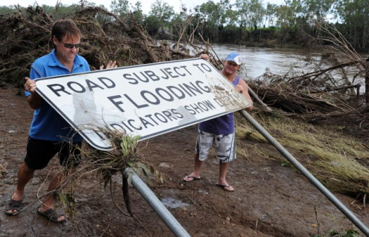 Greg Messenger (L) and Gary Clem (R) try to restore a flood warning sign which had been flattened by the swollen Burnett River on Jan. 2, 2011.  (Torsten Blackwood/AFP/Getty Images)