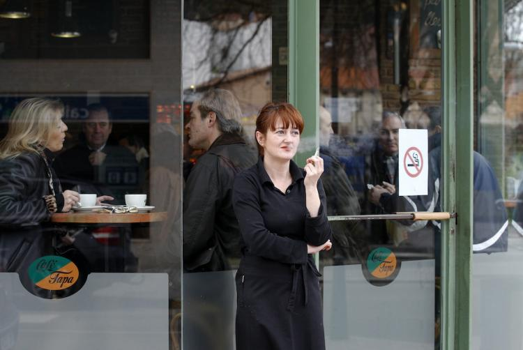 A woman smokes a cigarette outside a cafe in Burgos, Spain on January 2, following the introduction of a new law today banning smoking in all bars, restaurants and public places.   (Cesar Manso/Getty Images )