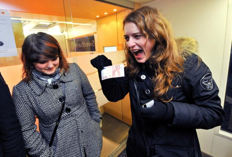 HAPPIER TIMES: A Estonian woman receives her first euro note from the ATM on Jan. 1, in Tallinn, Estonia.  (Raigo Pajula/Getty Images)