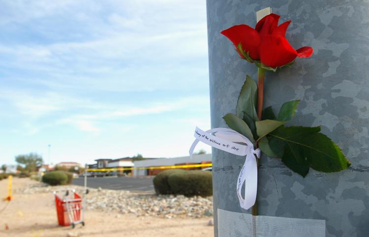 A single rose with the words 'In Memory of the victims of the Oracle and Ina Shooting' written on a ribbon is taped to a lamp post at the intersection of West Ina and North Oracle roads near the Safeway grocery store where a person allegedly opened fire on a group of people on January 9, 2011 in Tucson, Arizona. (Kevin C. Cox/Getty Images)