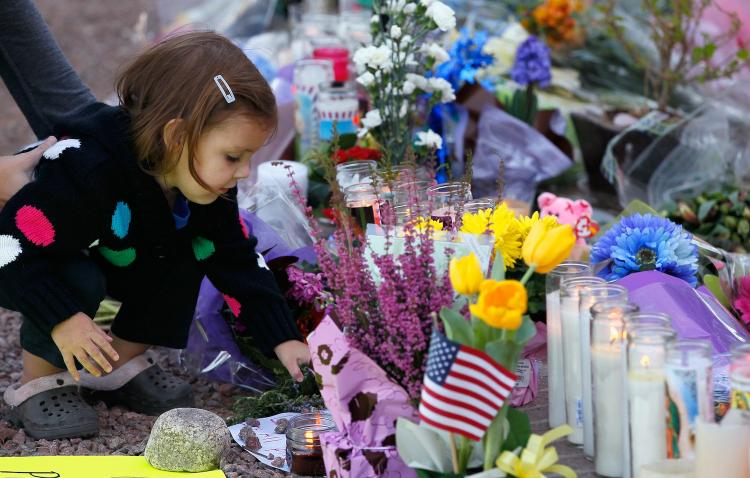 A young girl places a rock on a sign at the makeshift memorial outside of the District Office of U.S. Rep. Gabrielle Giffords (D-AZ) a day after a gunman opened fire during a public event at a Safeway store on January 9, in Tucson, Arizona.  ( Kevin C. Cox/Getty Images)