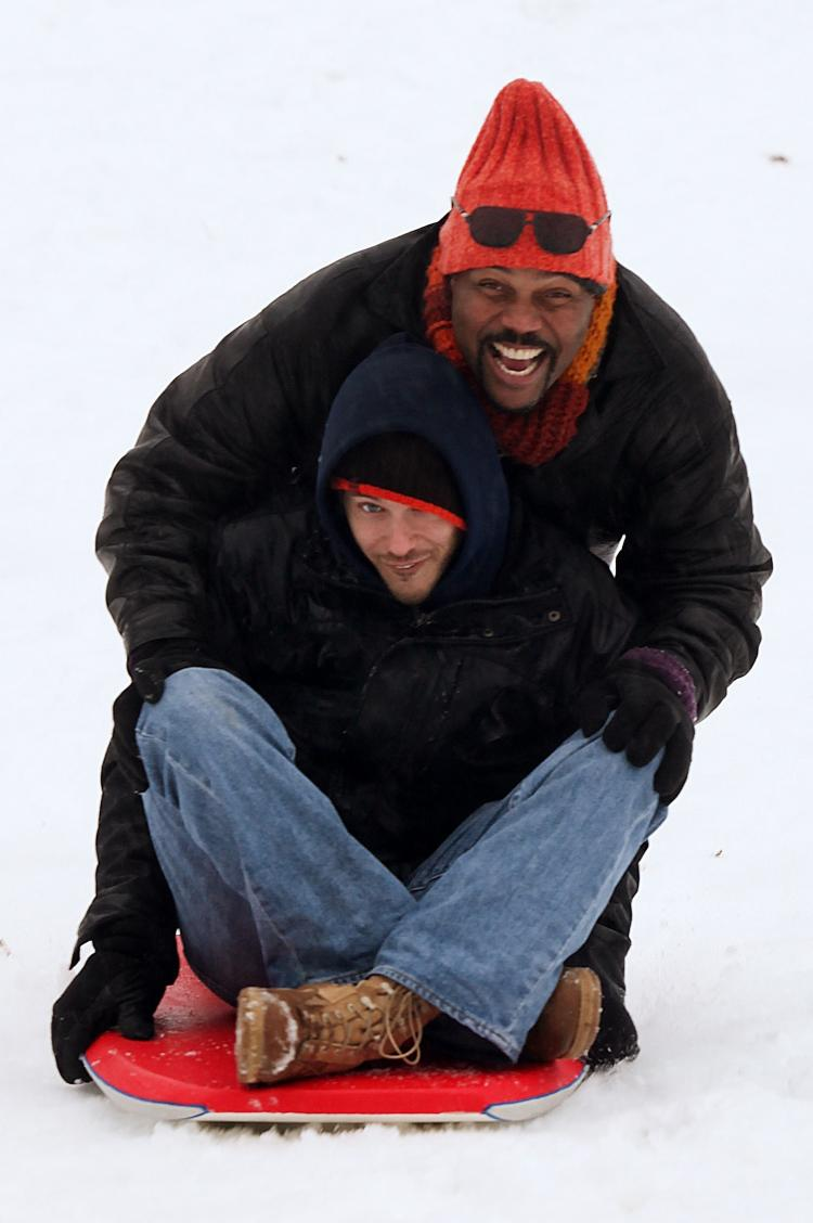 PLAYING: Friends Eric Coburn (top) and Troy Fortenberry sled down a hill in the Inman Park neighborhood after a snow storm on January 10, in Atlanta.   (Jessica McGowan/Getty Images)