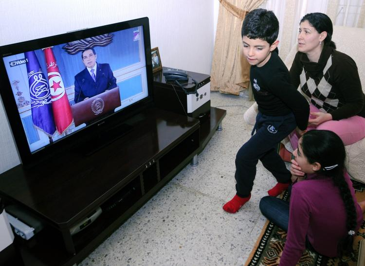 A Tunisian family watches a televised speech of President Zine el-Abidine Ben Ali. In an attempt to stop mounting protests in the country, Ben Ali promised to resign in 2014. But experts doubt whether Ben Ali will keep his promise.  (Fethi Belaid/AFP/Getty Images)