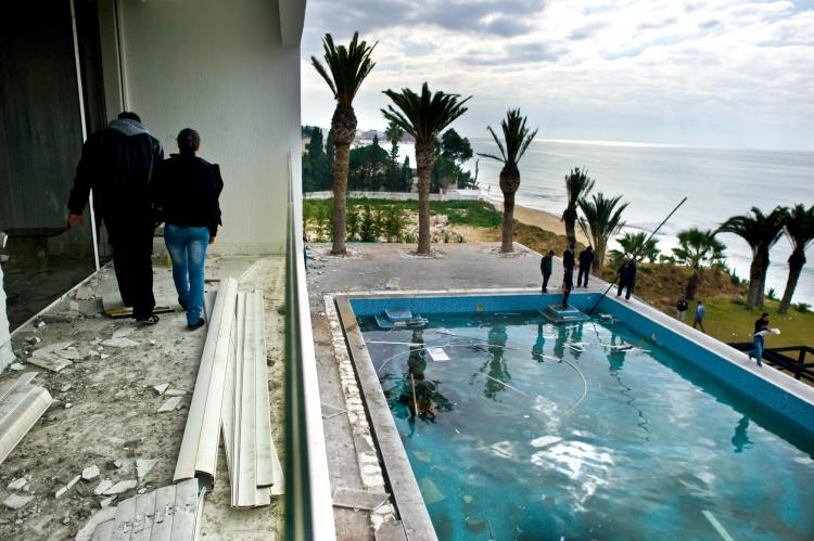 People walk on the balcony overlooking the pool as they visit the burnt and looted house that belonged to the nephew of ousted Tunisian President Zine El Abidine Ben Ali in Hammamet, some 37 miles southeast of Tunis, on Jan. 19.  (Martin Bureau/AFP/Getty Images)