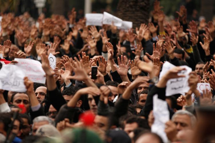 Tunisian demonstrators gesture with their hands calling to the army to pull down the Constitutional Democratic Rally (RCD) party headquarters sign on January 20, 2011 in Tunis, Tunisia. The success of Tunisia's Jasmine Revolution has caught the world's attention including the Chinese. (Christopher Furlong/Getty Images)