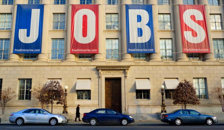 SLIGHT HINT: A pedestrian passes under a large banner reading 'JOBS' outside of the Chamber of Commerce Jan. 23 in Washington, D.C. Jobs and job creation are expected to be the centerpiece of President Barack Obama's State of the Union address on Jan. 25. (Mandel NGAN/Getty Images)