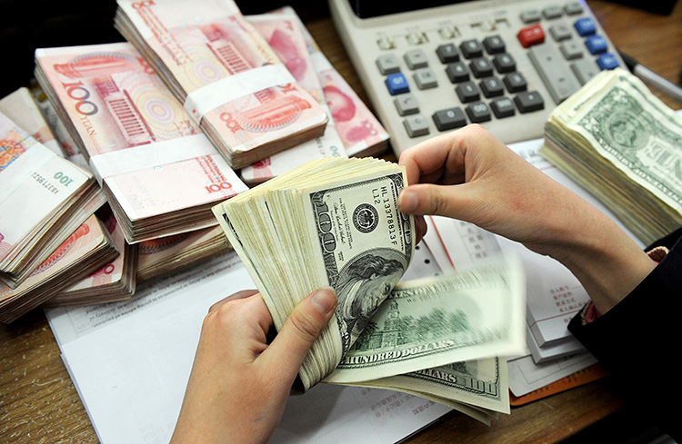 Stacks of US dollars and Chinese 100-yuan notes