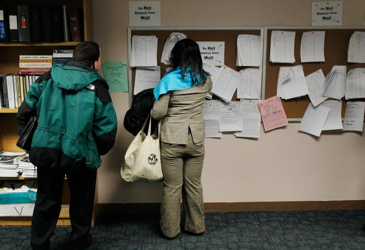 Unemployed people look over job listings on a board at a New York State Department of Labor Employment Services office March 3, 2011 in Brooklyn Borough of New York City. ( Chris Hondros/Getty Images)