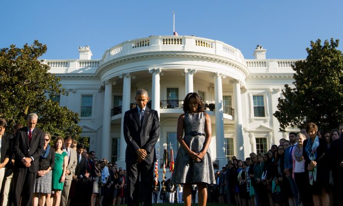 President Barack Obama, first lady Michelle Obama, and others, pause on the South Lawn of the White House in Washington, Friday, Sept. 11, 2015, as they observe a moment of silence to mark the 14th anniversary of the 9/11 attacks. (AP Photo/Andrew Harnik)