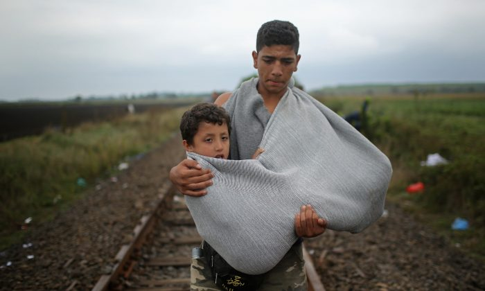 A youth carries a young boy in a makeshift sling as migrants walk towards waiting buses at the Hungarian border with Serbia on September 11, 2015 in Roszke, Hungary. (Christopher Furlong/Getty Images)