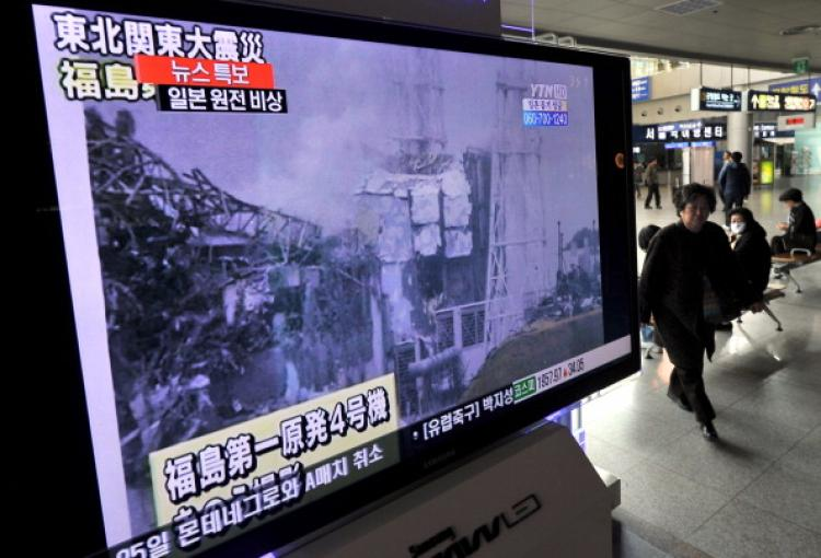 A South Korean passenger walks past a TV that is reporting an explosion and of Japan's Fukushima Daiichi Nuclear Power Plant last month. (Jung Yeon-Je/AFP/Getty Images)